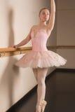 Όμορφο ballerina που στέκεται τη EN pointe μπάρα εκμετάλλευσης στοκ εικόνες