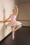 Όμορφο ballerina που στέκεται τη EN pointe μπάρα εκμετάλλευσης στοκ φωτογραφία