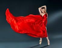 Όμορφο ballerina χορευτών που χορεύει ένα μακροχρόνιο κόκκινο πέταγμα φορεμάτων Στοκ Φωτογραφίες