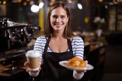 Όμορφο barista που κρατά το μίας χρήσης φλυτζάνι και brioche Στοκ φωτογραφία με δικαίωμα ελεύθερης χρήσης