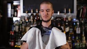 Όμορφο bartender είναι χαμόγελο, σκουπίζοντας ένα γυαλί στεμένος στο μετρητή φραγμών στο μπαρ απόθεμα βίντεο