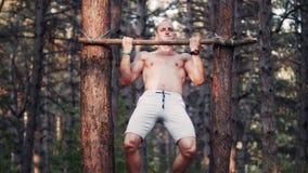 Όμορφο bodybuilder που κάνει το τράβηγμα-UPS στο δάσος απόθεμα βίντεο