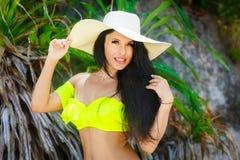 Όμορφο brunette με μακρυμάλλη στο καπέλο μπικινιών και αχύρου Στοκ Φωτογραφία