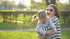 Όμορφο Brunette με τα γυαλιά ηλίου φέρνει λίγο χαριτωμένο κορίτσι σε ετοιμότητα και Whirling αυτή Υπαίθρια πορτρέτο ευτυχούς απόθεμα βίντεο