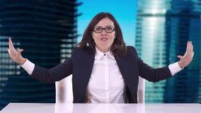 Όμορφο brunette με τα γυαλιά που κάθονται σε ένα επιχειρησιακό κοστούμι στο γραφείο γραφείων και τις κραυγές απόθεμα βίντεο
