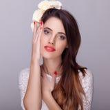Όμορφο brunette με τα λουλούδια στο επικεφαλής και κόκκινο κραγιόν Στοκ Φωτογραφία