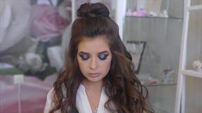 Όμορφο brunette με τη σύνθεση και hairstyle, εξετάζοντας τη κάμερα απόθεμα βίντεο