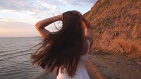 Όμορφο brunette με το μακρυμάλλες τρέξιμο στην παραλία στο υπόβαθρο ηλιοβασιλέματος απόθεμα βίντεο