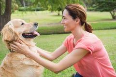 Όμορφο brunette με το σκυλί της στο πάρκο Στοκ Εικόνες