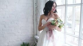 Όμορφο brunette νυφών που στέκεται στο γαμήλιο φόρεμα με την ανθοδέσμη κοντά στο παράθυρο απόθεμα βίντεο