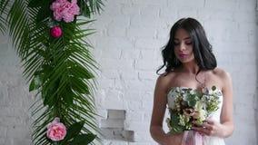 Όμορφο brunette νυφών που στέκεται στο γαμήλιο φόρεμα με την ανθοδέσμη κοντά στο παράθυρο φιλμ μικρού μήκους
