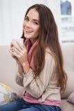 Όμορφο brunette που έχει τον καφέ στον καναπέ Στοκ Εικόνες