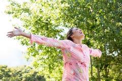 Όμορφο brunette που αισθάνεται ελεύθερο στο πάρκο Στοκ εικόνες με δικαίωμα ελεύθερης χρήσης