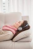 Όμορφο brunette που ακούει τη μουσική στον καναπέ Στοκ Φωτογραφίες