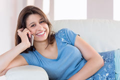 Όμορφο brunette που κάνει μια κλήση στον καναπέ Στοκ Εικόνα