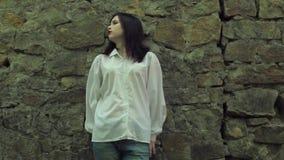 Όμορφο brunette που ονειρεύεται και λυπημένο, στεμένος κοντά σε έναν τοίχο πετρών απόθεμα βίντεο