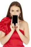 Όμορφο brunette που παρουσιάζει έξυπνο τηλέφωνο στο άσπρο υπόβαθρο Στοκ Εικόνα