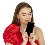 Όμορφο brunette που παρουσιάζει έξυπνο τηλέφωνο στο άσπρο υπόβαθρο Στοκ Εικόνες