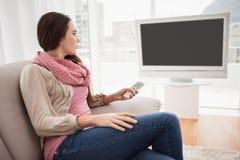Όμορφο brunette που προσέχει τη TV στον καναπέ Στοκ εικόνα με δικαίωμα ελεύθερης χρήσης