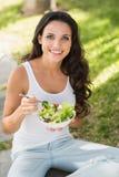 Όμορφο brunette που τρώει το κύπελλο της σαλάτας Στοκ Εικόνα