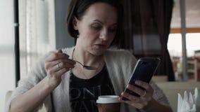 Όμορφο brunette που τρώει cheesecake με ένα smartphone διαθέσιμο απόθεμα βίντεο