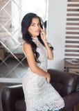 Όμορφο brunette σε ένα άσπρο φόρεμα στο εσωτερικό στοκ εικόνα