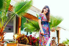 Όμορφο brunette σε ένα ζωηρόχρωμο μακρύ φόρεμα που στέκεται στην παραλία κοντά στο φραγμό στο υπόβαθρο των φοινίκων Στοκ Φωτογραφίες