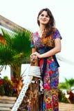 Όμορφο brunette σε ένα ζωηρόχρωμο μακρύ φόρεμα που στέκεται στην παραλία κοντά στο φραγμό στο υπόβαθρο των φοινίκων Στοκ Φωτογραφία
