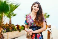 Όμορφο brunette σε ένα ζωηρόχρωμο μακρύ φόρεμα που στέκεται στην παραλία κοντά στο φραγμό στο υπόβαθρο των φοινίκων Στοκ Εικόνες