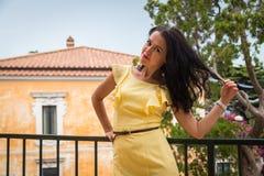 Όμορφο brunette σε ένα κίτρινο φόρεμα Στοκ Φωτογραφία