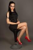 Όμορφο brunette σε ένα μαύρο φόρεμα και τα γυαλιά ηλίου που θέτουν το sittin Στοκ Φωτογραφία