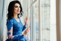 Όμορφο brunette σε ένα μπλε φόρεμα σε ένα ευρύ παράθυρο Μια γυναίκα σε ένα κομψό εσωτερικό εσωτερικό στούντιο Στοκ Εικόνες