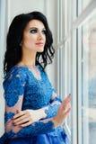 Όμορφο brunette σε ένα μπλε φόρεμα σε ένα ευρύ παράθυρο Μια γυναίκα σε ένα κομψό εσωτερικό εσωτερικό στούντιο Στοκ φωτογραφία με δικαίωμα ελεύθερης χρήσης