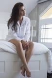 Όμορφο brunette σε μια άσπρη τοποθέτηση πουκάμισων σε ένα κρεβάτι στοκ φωτογραφίες με δικαίωμα ελεύθερης χρήσης
