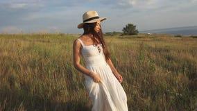 Όμορφο brunette σε μια τοποθέτηση καπέλων στον τομέα απόθεμα βίντεο