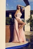Όμορφο brunette στην πολυτελή τοποθέτηση φορεμάτων μεταξιού στο θερινό κήπο στοκ φωτογραφία με δικαίωμα ελεύθερης χρήσης