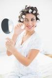 Όμορφο brunette στους κυλίνδρους τρίχας που φαίνονται διαθέσιμος καθρέφτης και χρησιμοποίηση χεριών Στοκ εικόνα με δικαίωμα ελεύθερης χρήσης