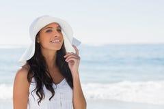 Όμορφο brunette στο άσπρο ψαθάκι που κοιτάζει μακριά και σχετικά με το καπέλο Στοκ εικόνες με δικαίωμα ελεύθερης χρήσης