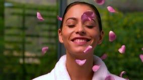 Όμορφο brunette στο μπουρνούζι στη SPA που ρίχνει επάνω στα ροδαλά πέταλα απόθεμα βίντεο