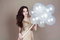 Όμορφο brunette στο πολυτελές φόρεμα που κρατά τα άσπρα μπαλόνια Στοκ Εικόνα