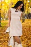 Όμορφο brunette στο φόρεμα μόδας στο υπόβαθρο του πάρκου φθινοπώρου Στοκ Εικόνες