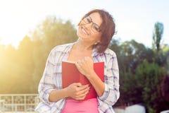 Όμορφο brunette χαμόγελου που χαλαρώνει υπαίθρια και ανάγνωση του βιβλίου ύφος ανασκόπησης αστικό Στοκ φωτογραφίες με δικαίωμα ελεύθερης χρήσης