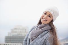Όμορφο brunette χαμόγελου με τα χειμερινά ενδύματα στην τοποθέτηση Στοκ φωτογραφία με δικαίωμα ελεύθερης χρήσης