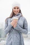 Όμορφο brunette χαμόγελου με τα χειμερινά ενδύματα στον καφέ εκμετάλλευσης Στοκ εικόνα με δικαίωμα ελεύθερης χρήσης
