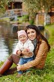 Όμορφο brunette mom που κρατά ένα γοητευτικό όμορφο μικρό κορίτσι Στοκ φωτογραφία με δικαίωμα ελεύθερης χρήσης