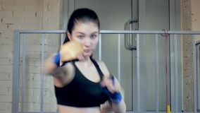 Όμορφο kickboxing punching κατάρτισης γυναικών με τη λαστιχένια ζώνη ικανότητας κατάλληλο σώμα δύναμης στούντιο στο άγριο kickbox φιλμ μικρού μήκους