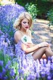Όμορφο lavender συνεδρίασης νέων κοριτσιών ανθίζοντας πλησίον Στοκ Εικόνα