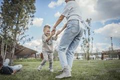 Όμορφο mum που γυρίζει γύρω, που με το γιο της στο πάρκο r στοκ φωτογραφία