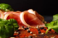 Όμορφο prosciutto με τα πράσινα φύλλα σπανακιού Περικοπή jamon με το πιπέρι σε ένα μαύρο υπόβαθρο εύγευστο κρέας Εστιατόριο Στοκ Εικόνες
