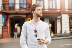 Όμορφο redhead γενειοφόρο άτομο με το μοντέρνο κούρεμα στο άσπρο πουκάμισο που περπατά γύρω από την πόλη και τον καφέ κατανάλωσης Στοκ φωτογραφίες με δικαίωμα ελεύθερης χρήσης